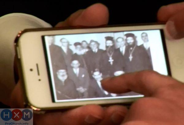 Пастор Бенни Хинн показывает на телефон фото своего отца в окружении православных священников